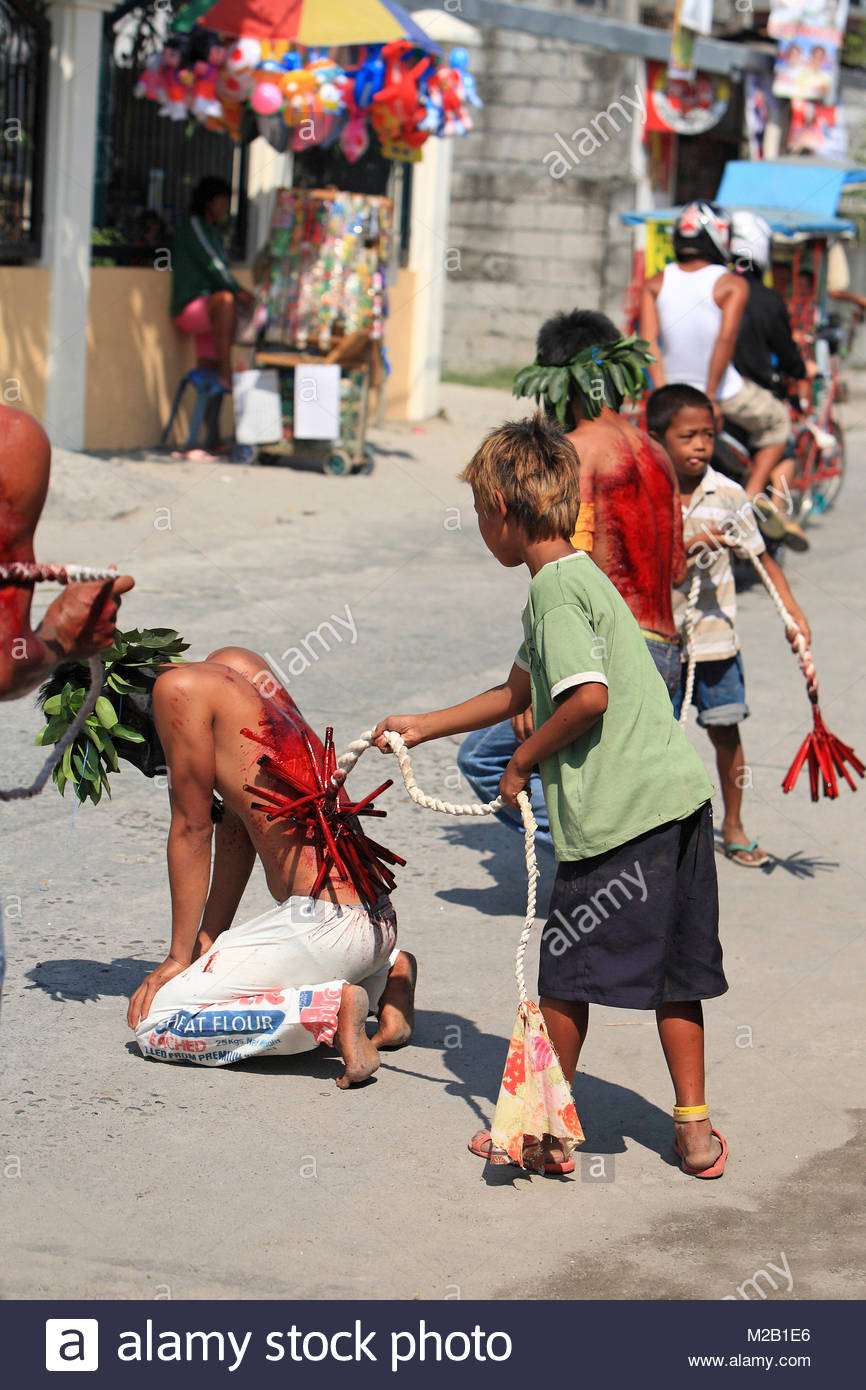 Kids beating a flagellant, bloody ritual, bloody procession annual Good Friday, Easter, San Pedro Cutud, Luzon, - Stock Image
