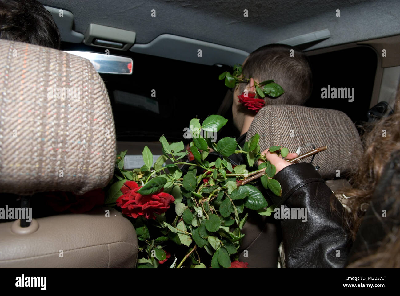 night shot of car interior with a woman holding out a bunch of roses to male passenger who has a rose behind his - Stock Image