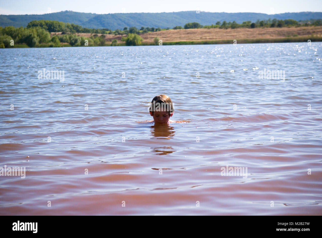 a ten year old boy, with only his head above water, looks down into the murky pink water of Lac de Salagou in the - Stock Image