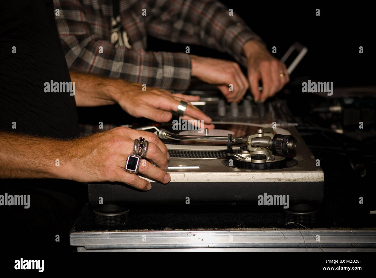 close up of two DJs hands playing vinyls on their record decks at a party in a nightclub - Stock Image