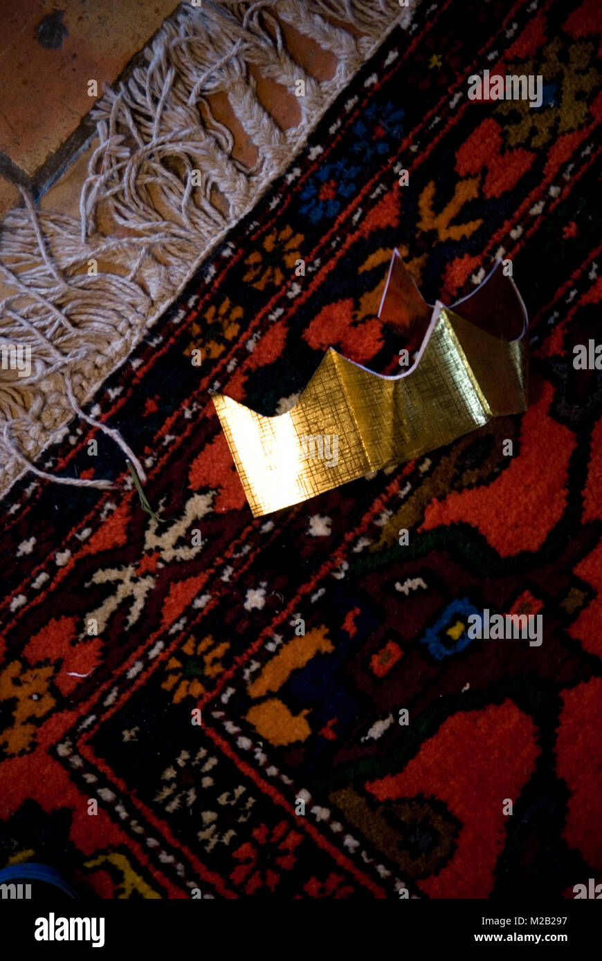 close up of paper gold paper crown from christmas cracker lying on moroccan rug on floor - Stock Image
