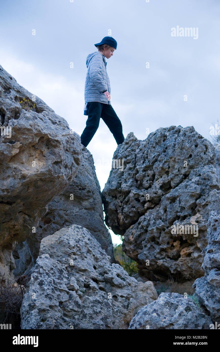 an eleven year old boy strides across two rocks , Cirque du moureze, France - Stock Image