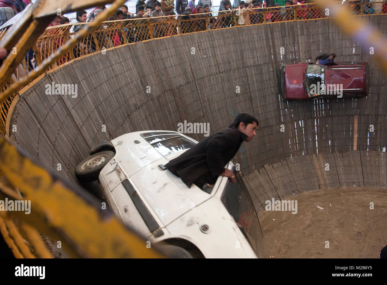 Men perform car stunt in a circus called death of bowl in Nepal. - Stock Image