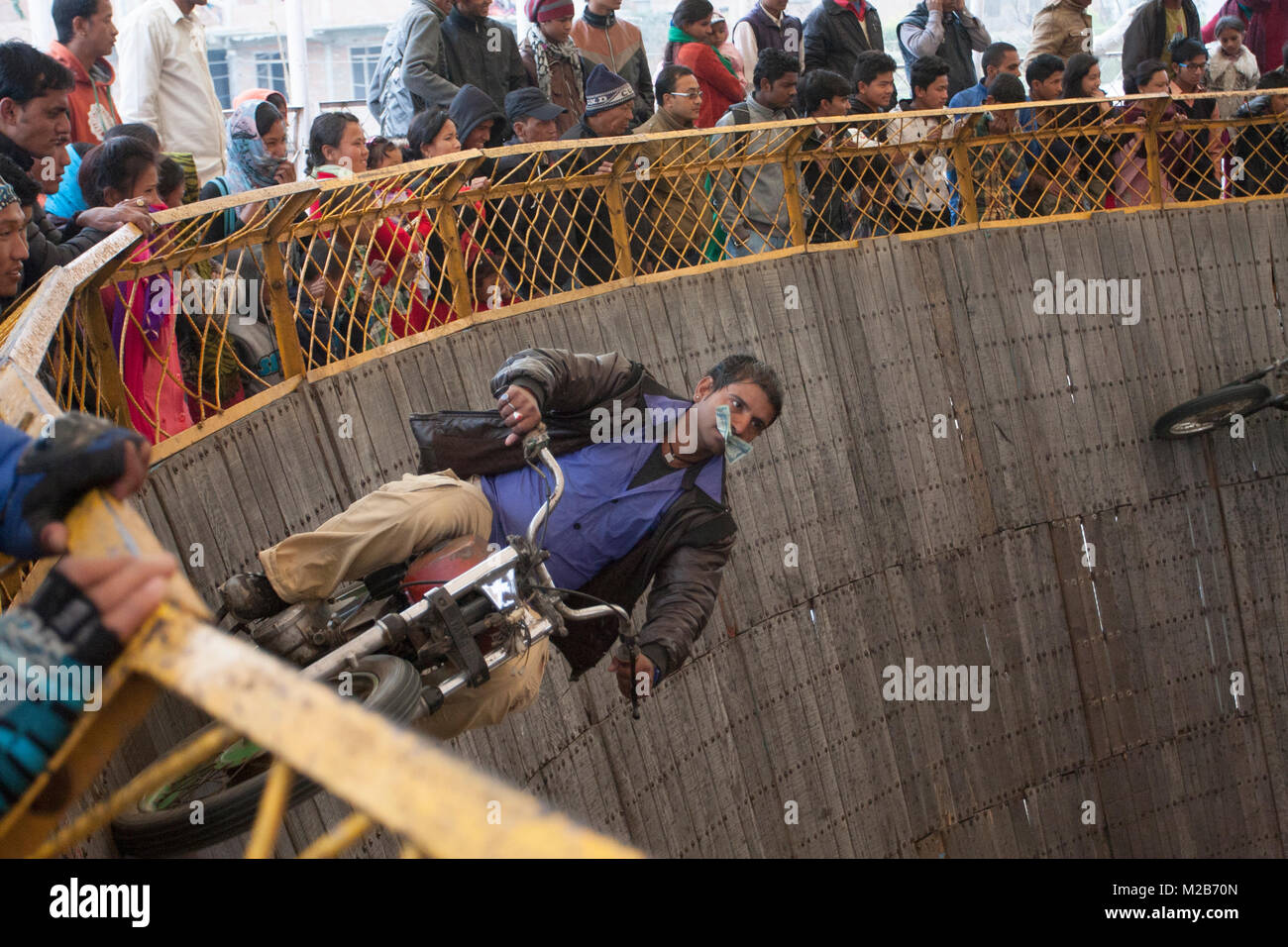 A biker performs stunt in a circus called death of bowls in Nepal. Stock Photo