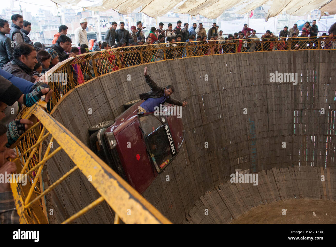 A man performs car stunt in a circus called death of bowl in Nepal. - Stock Image
