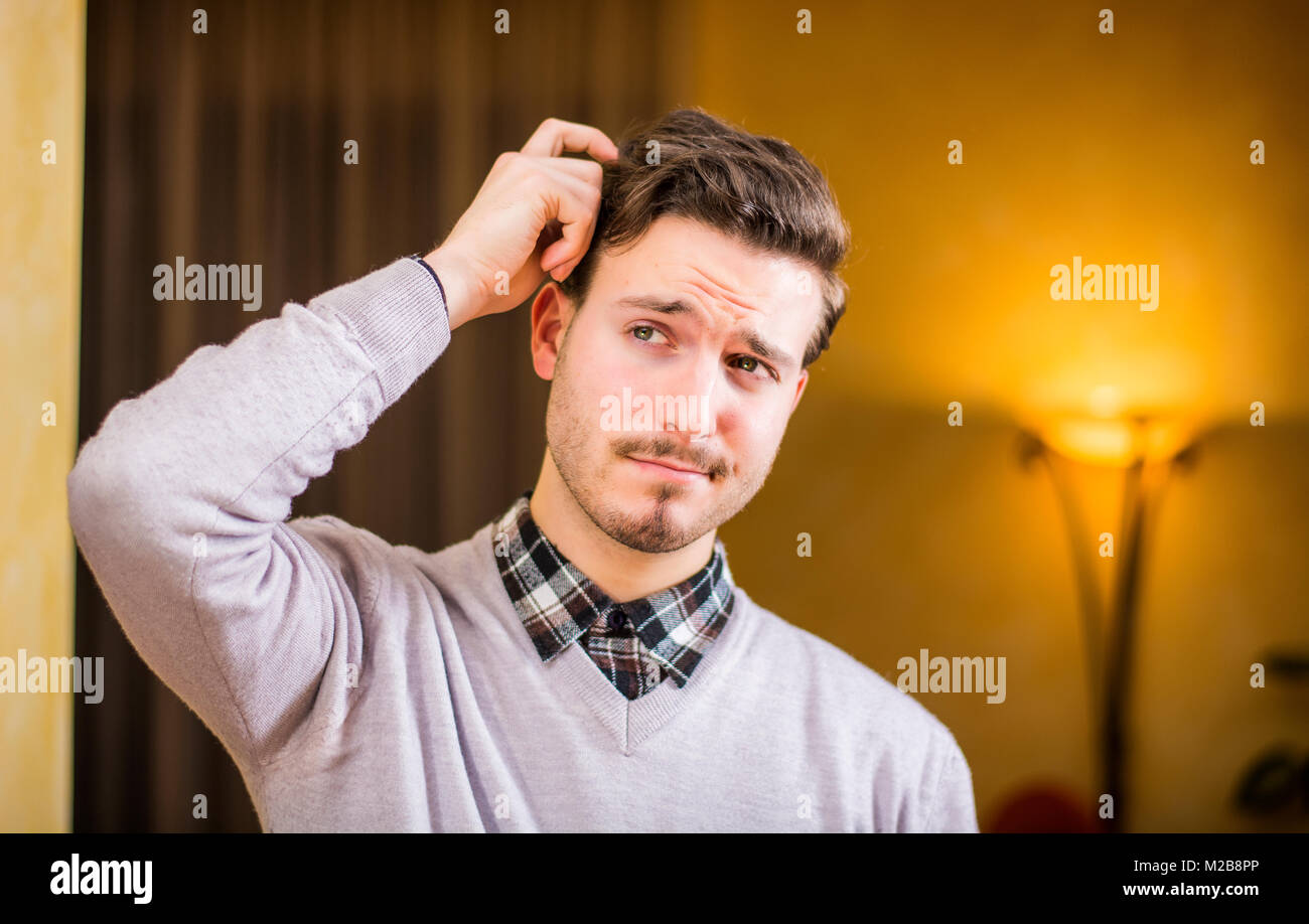 Confused or doubtful young man scratching his head and looking up - Stock Image