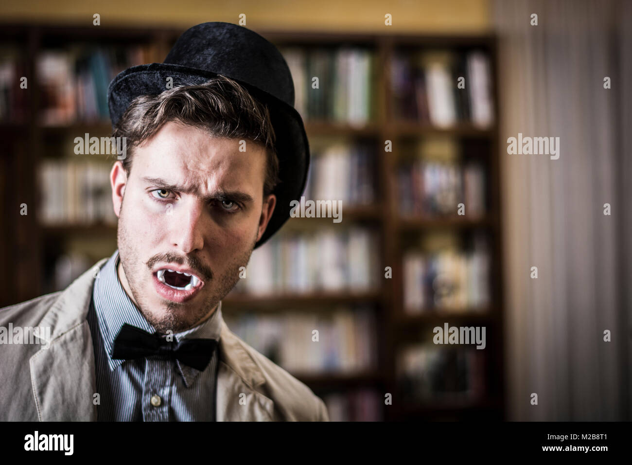 Close up Young Handsome White Vampire with Black Top Hat - Stock Image