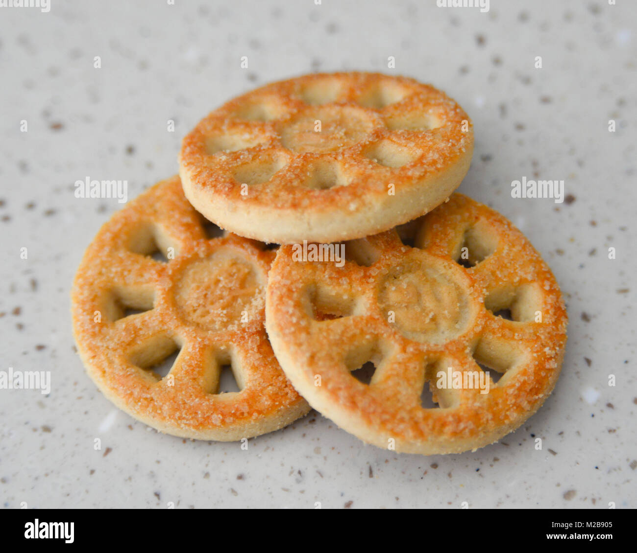 Close up of three round biscuits on a beige surface - Stock Image