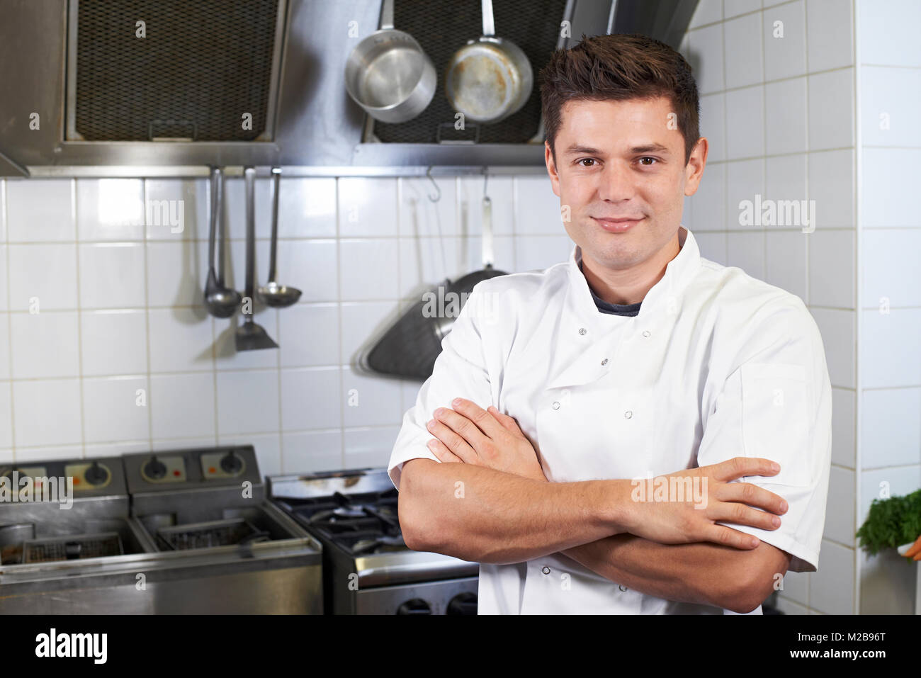 Portrait Of Chef Wearing Whites Standing By Cooker In Kitchen - Stock Image