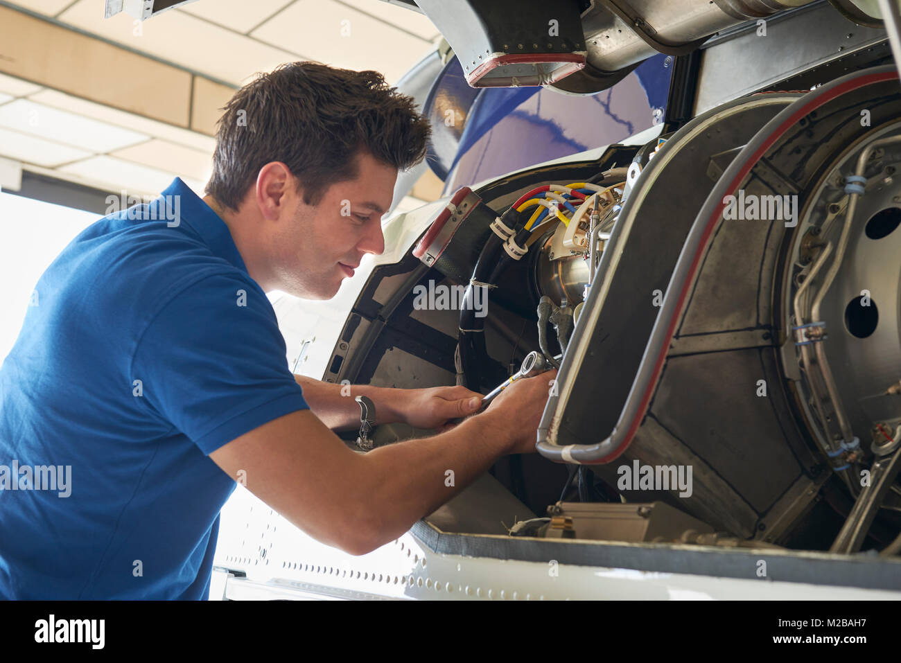 Male Aero Engineer Working On Helicopter In Hangar - Stock Image