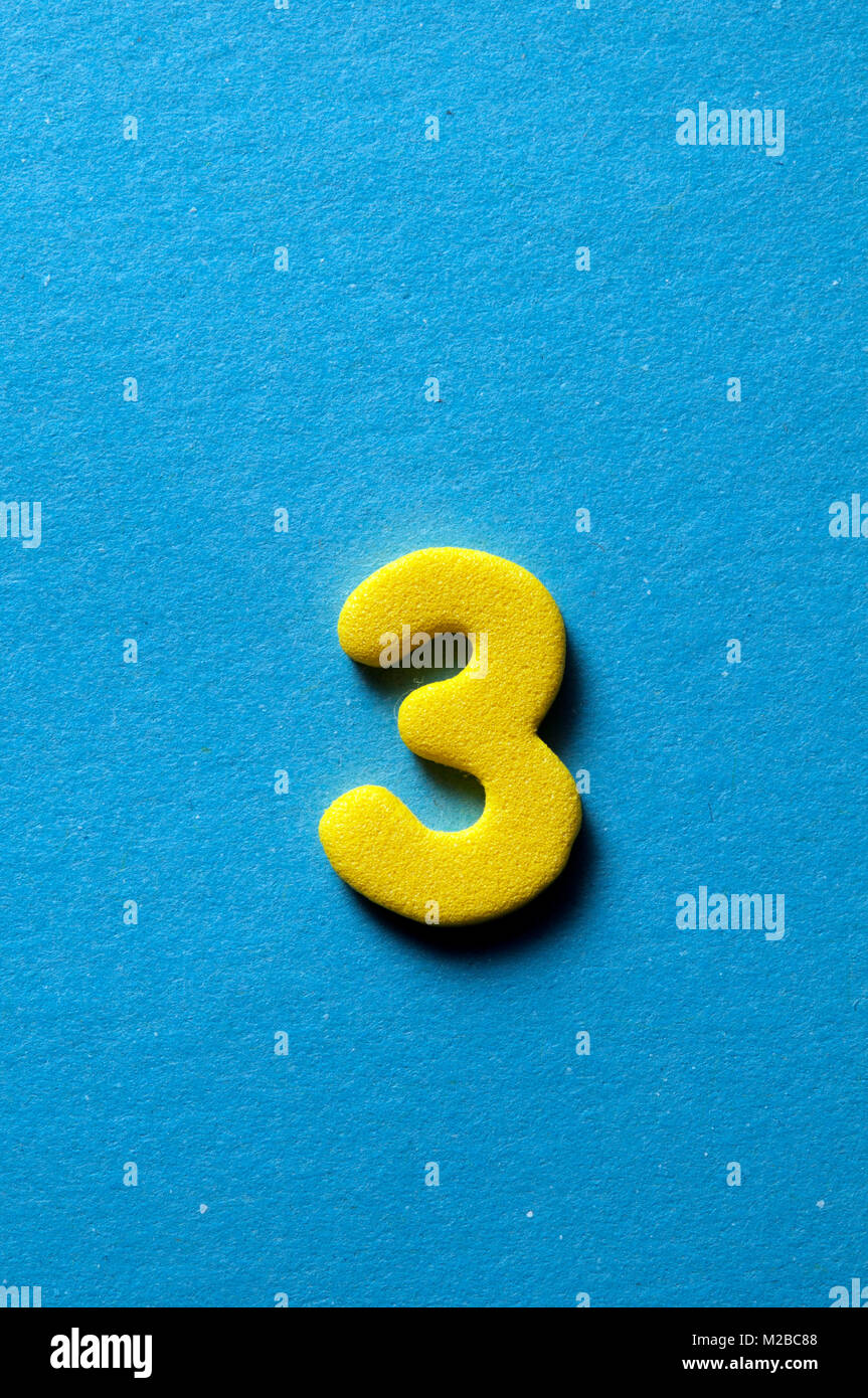 yellow number three on blue background - Stock Image