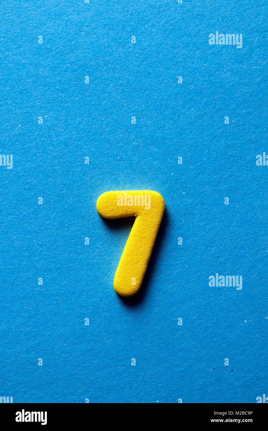 yellow number seven on blue background - Stock Image