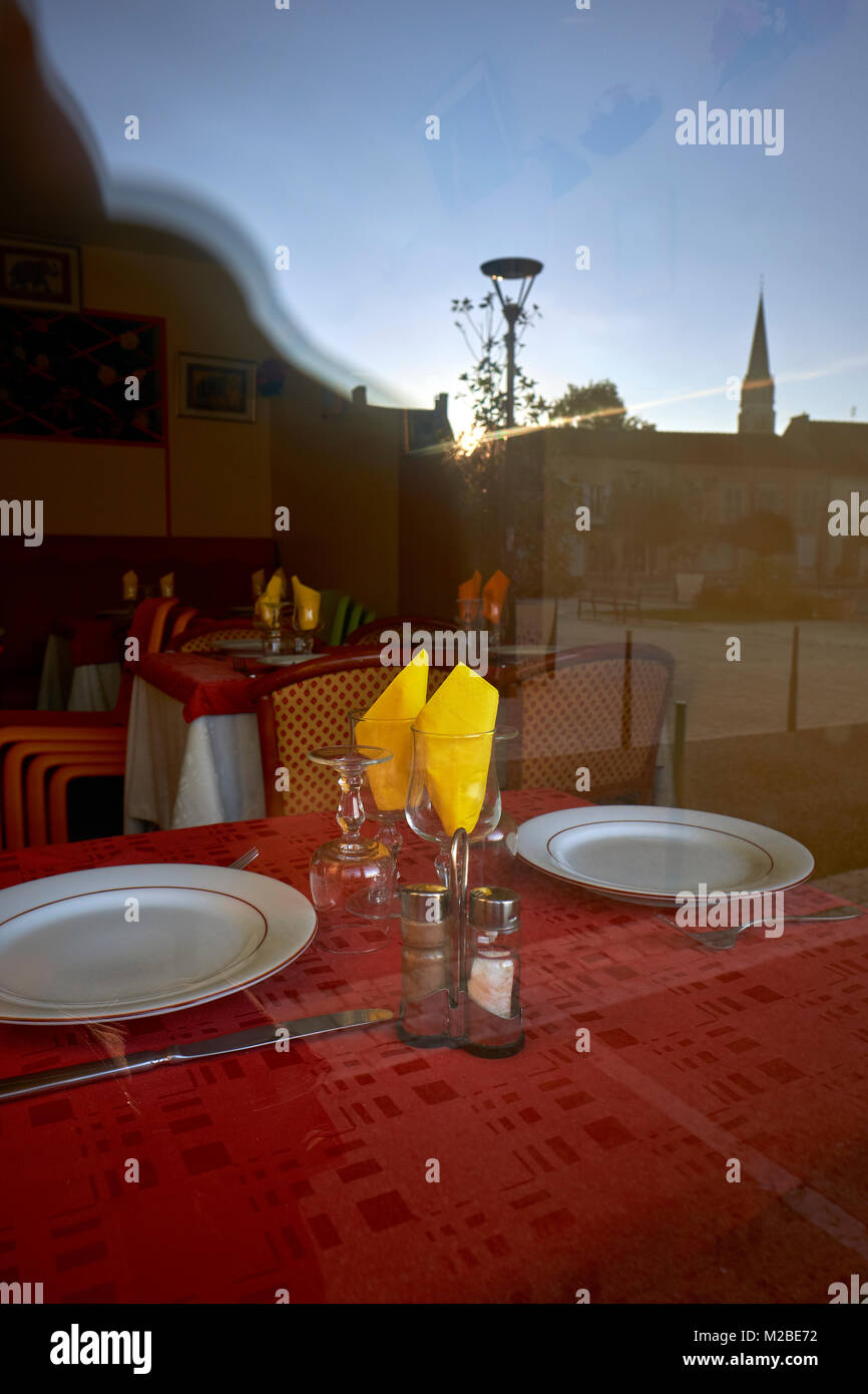 Yellow napkins and a red table cloth of a restaurant window - Stock Image