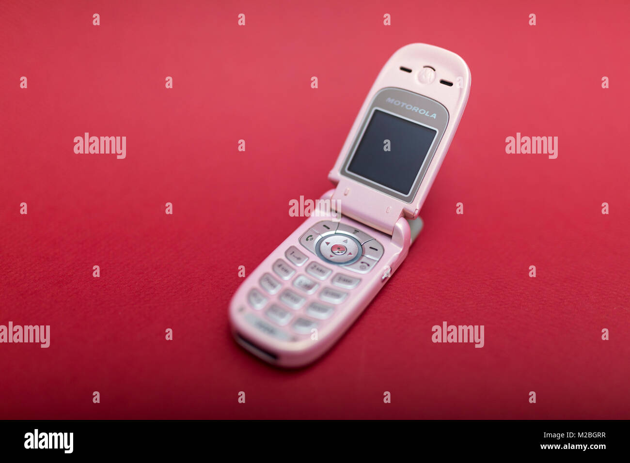 Cool and classic Motorola V220 pink retro flip cell or mobile phone isolated against a red background - Stock Image