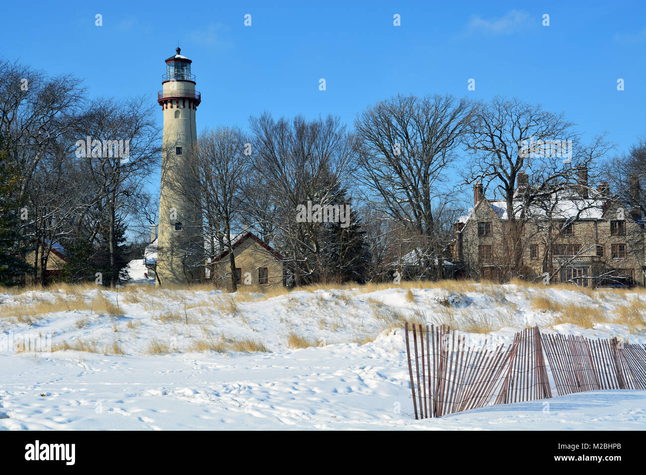 Snow covers the beach and dunes at Grosse Point where the lighthouse, completed in 1874, marks a shoal in Lake Michigan - Stock Image