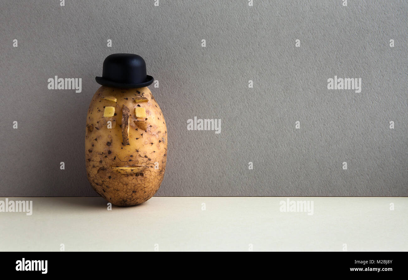 Senor Potato bowler hat serious face. Old fashioned style vegetable on gray wall background. Copy space - Stock Image