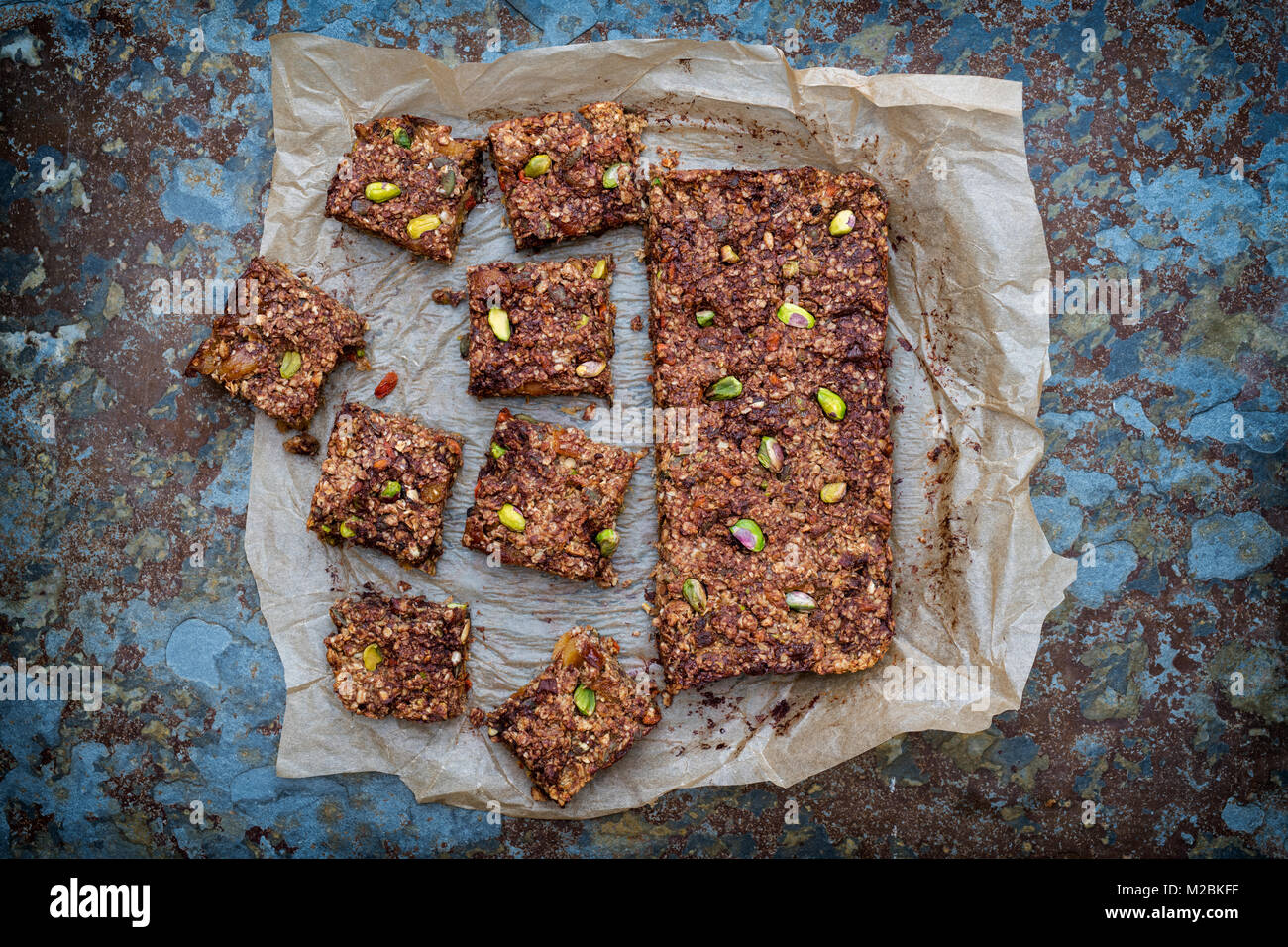 Homemade seed, nut, dried fruit and dark chocolate Oat Energy bars on baking parchment on slate background - Stock Image