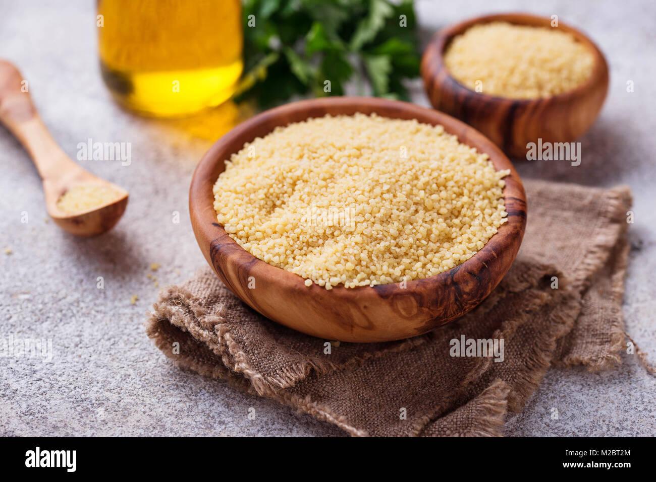 Couscous grain in wooden bowl  - Stock Image