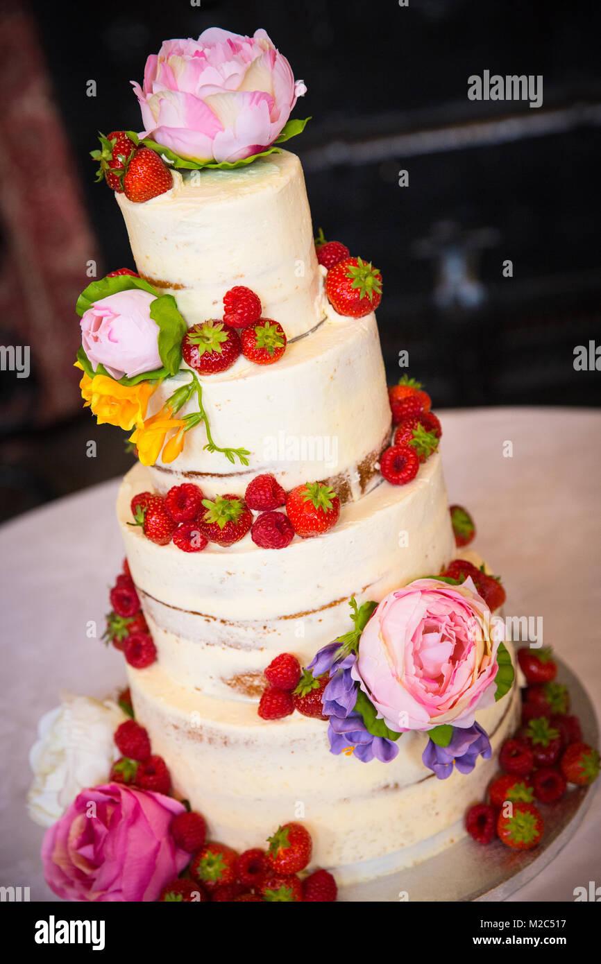 Fresh flowers and fruit on tiered celebration cake - Stock Image