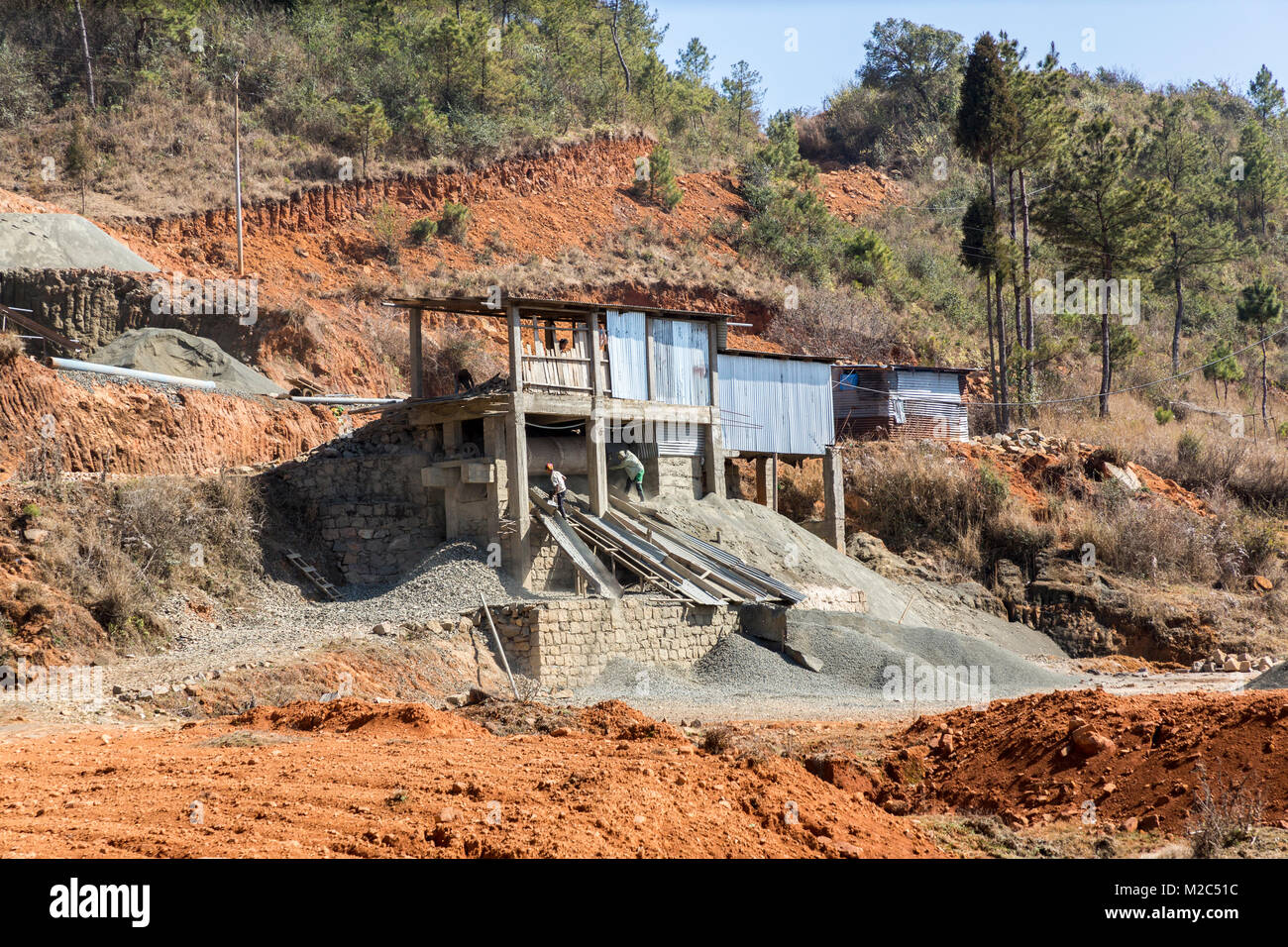 Men working a stone crusher to create gravel, on way from Mawsynram to Shillong, Meghalaya, India - Stock Image