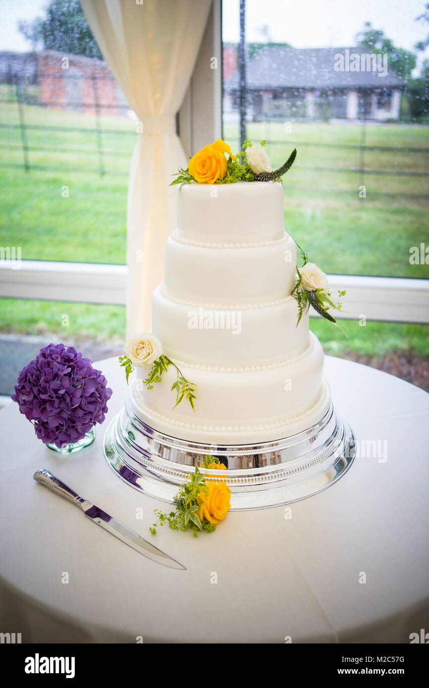 Three tiered celebration cake decorated with fresh flowers - Stock Image
