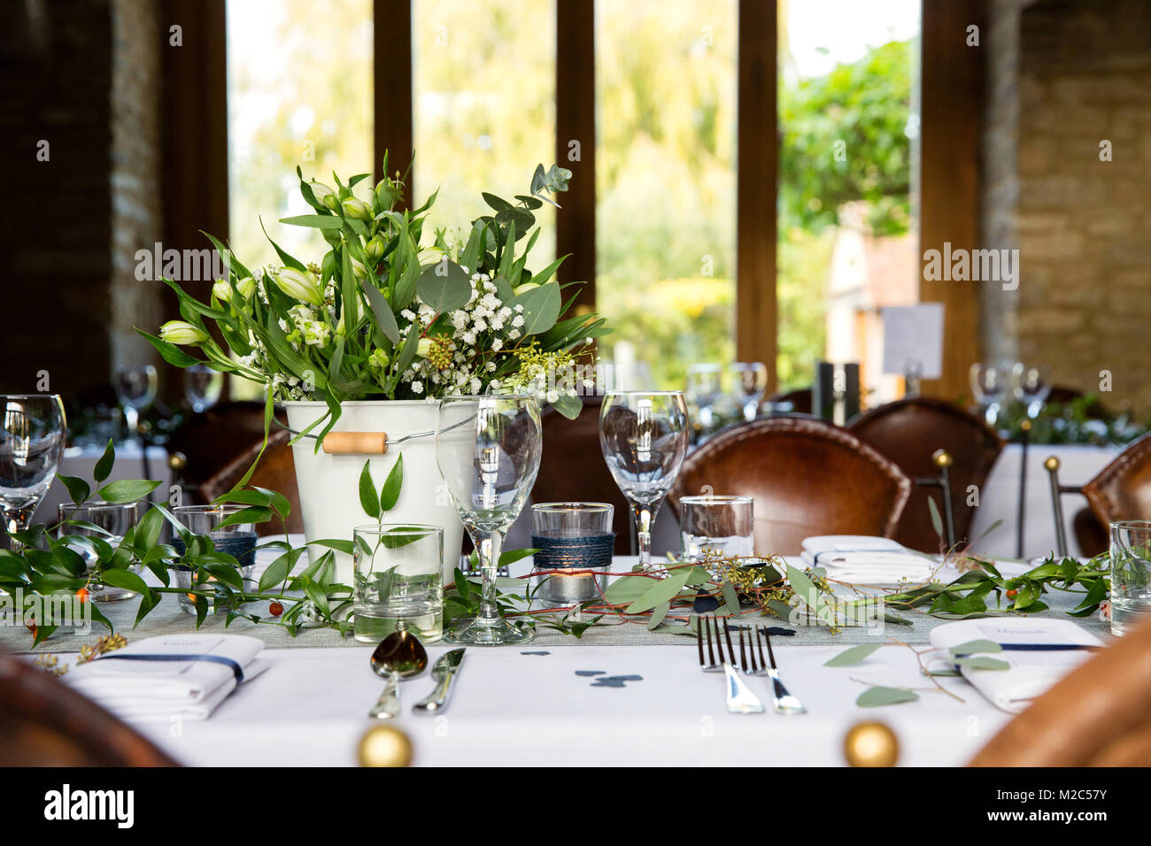 Table laid with place settings, floral arrangement and glassware - Stock Image