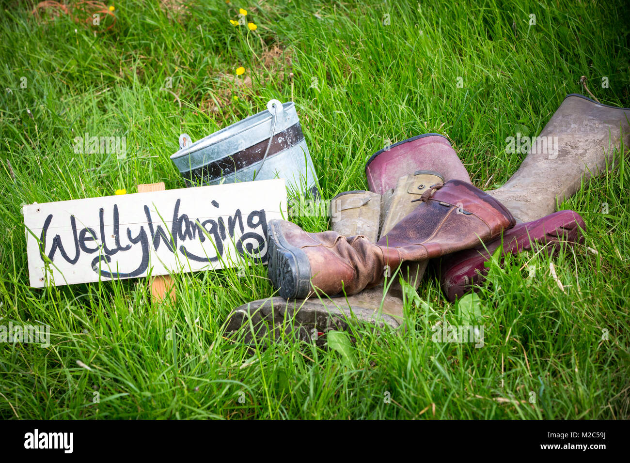 Pile of boots on grass in field, with handwritten 'Welly Wanging' sign Stock Photo