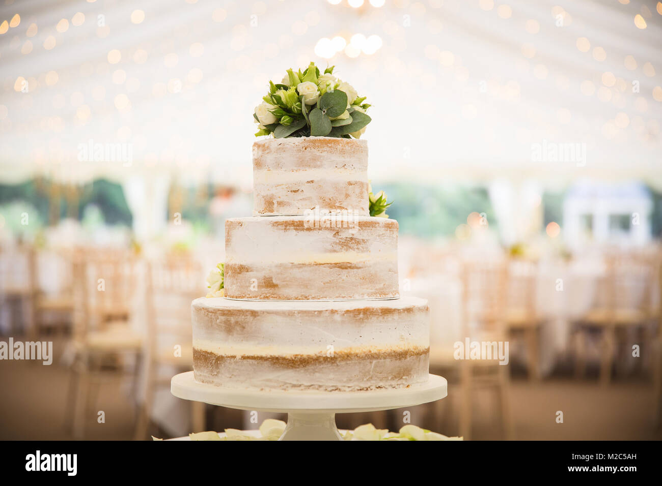 Three tiered wedding cake topped with flowers, in empty marquee - Stock Image