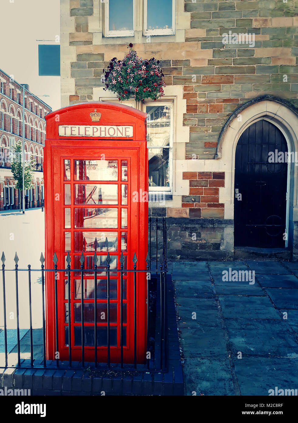 Traditional british red phone booth on the street near Guidhall, Northampton, England. - Stock Image