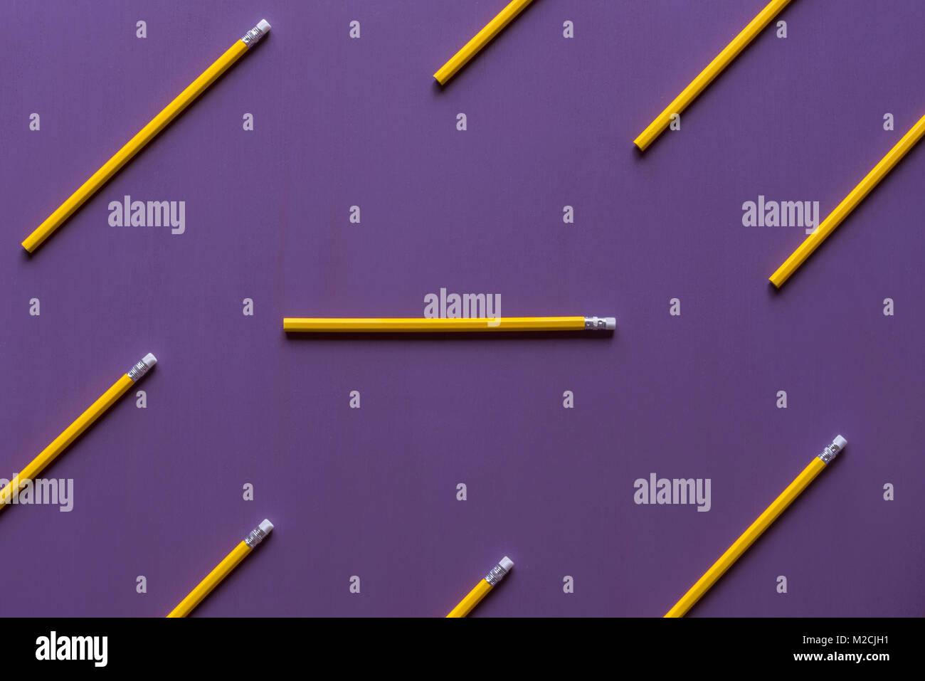 Wooden pencils with eraser tops arranged parallelly and only  one in horizontally, out of context, with space for - Stock Image