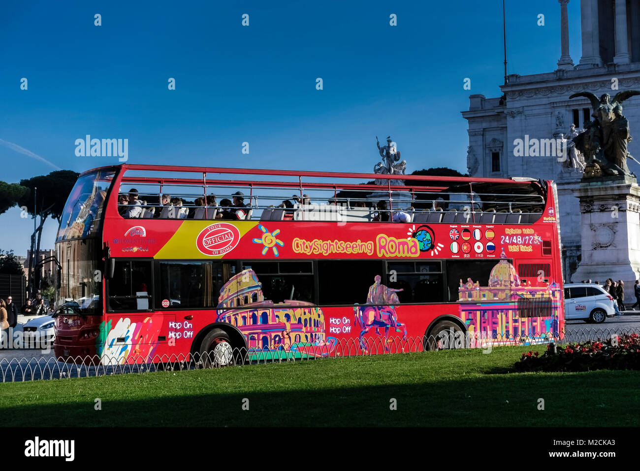 Tourist sightseeing, hop on hop off, red double decker bus, passing through Venice Square. Rome, Italy, Europe. - Stock Image