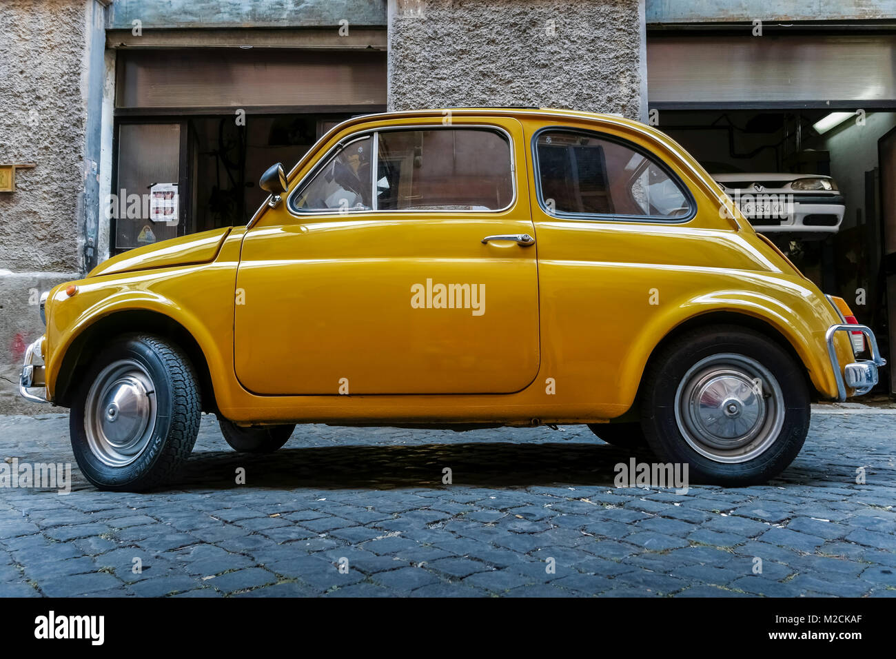 Fiat 500 fabricated in 1970. Old style, classic, vintage, retro car. Yellow color. Parked outside an auto repair - Stock Image