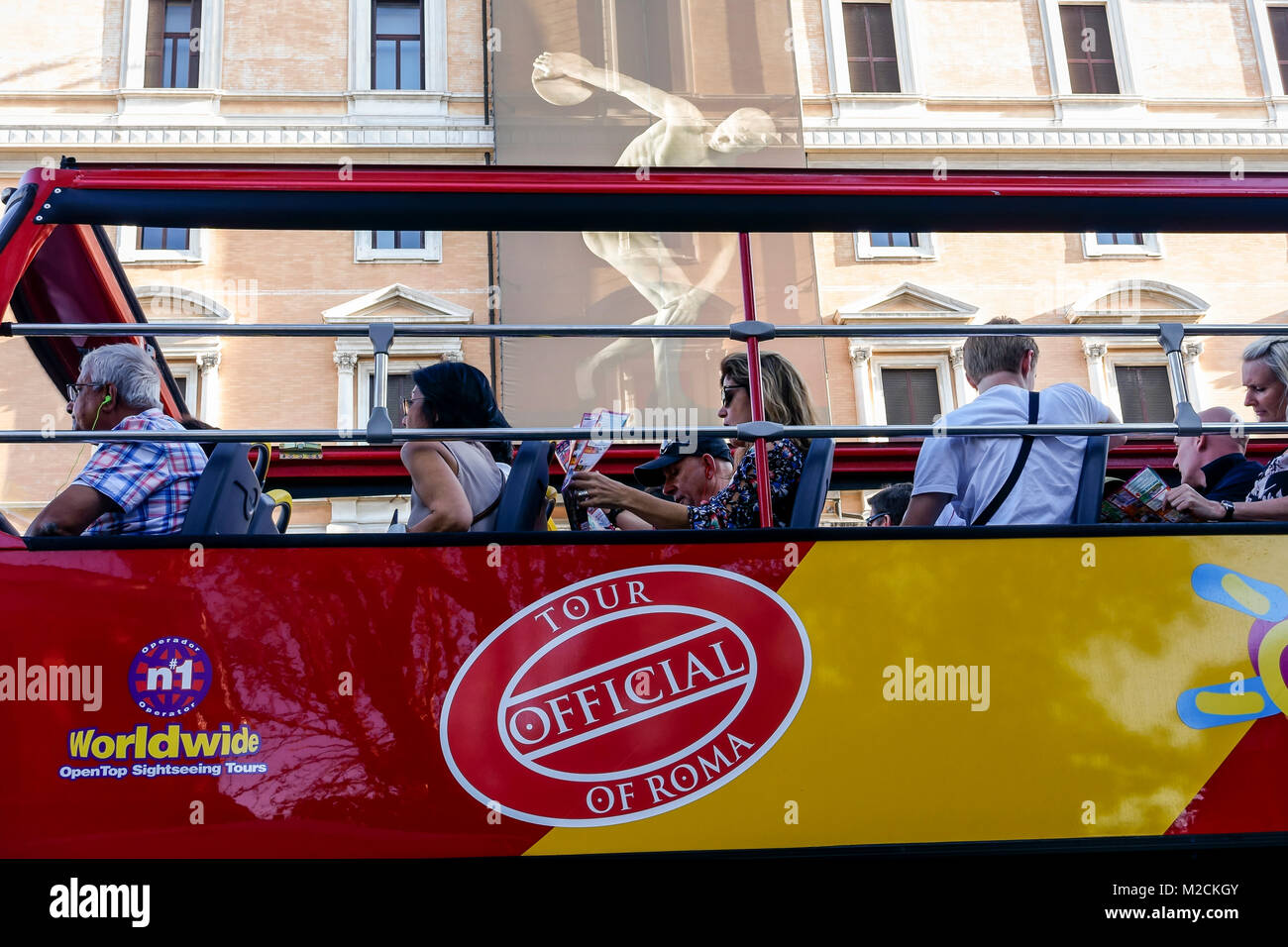 Tourist sightseeing red double decker bus passing in front of Palazzo Massimo alle Terme, National Roman Museum. - Stock Image