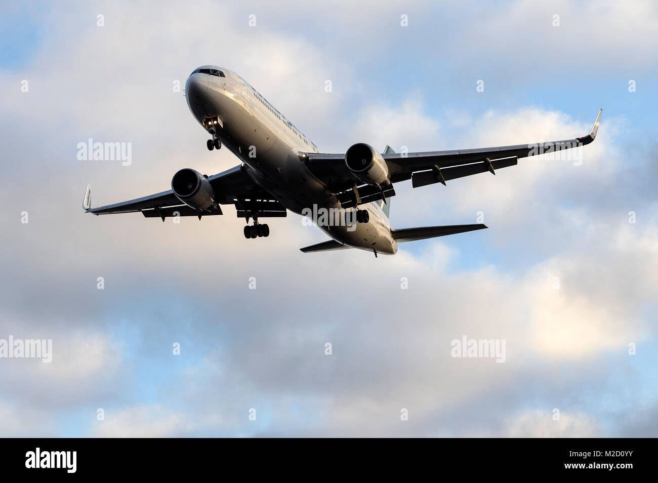 A WestJet Airlines Boeing 767-300ER aircraft on final approach to London Gatwick airport on a January morning - Stock Image