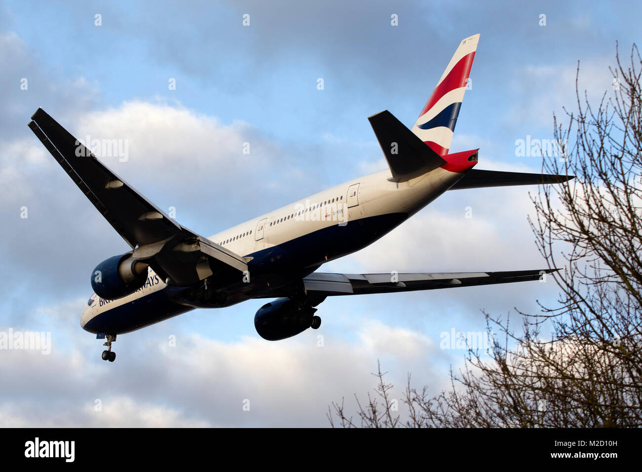 A British Airways Boeing 777 aircraft on final approach to London Gatwick airport on a January morning - Stock Image