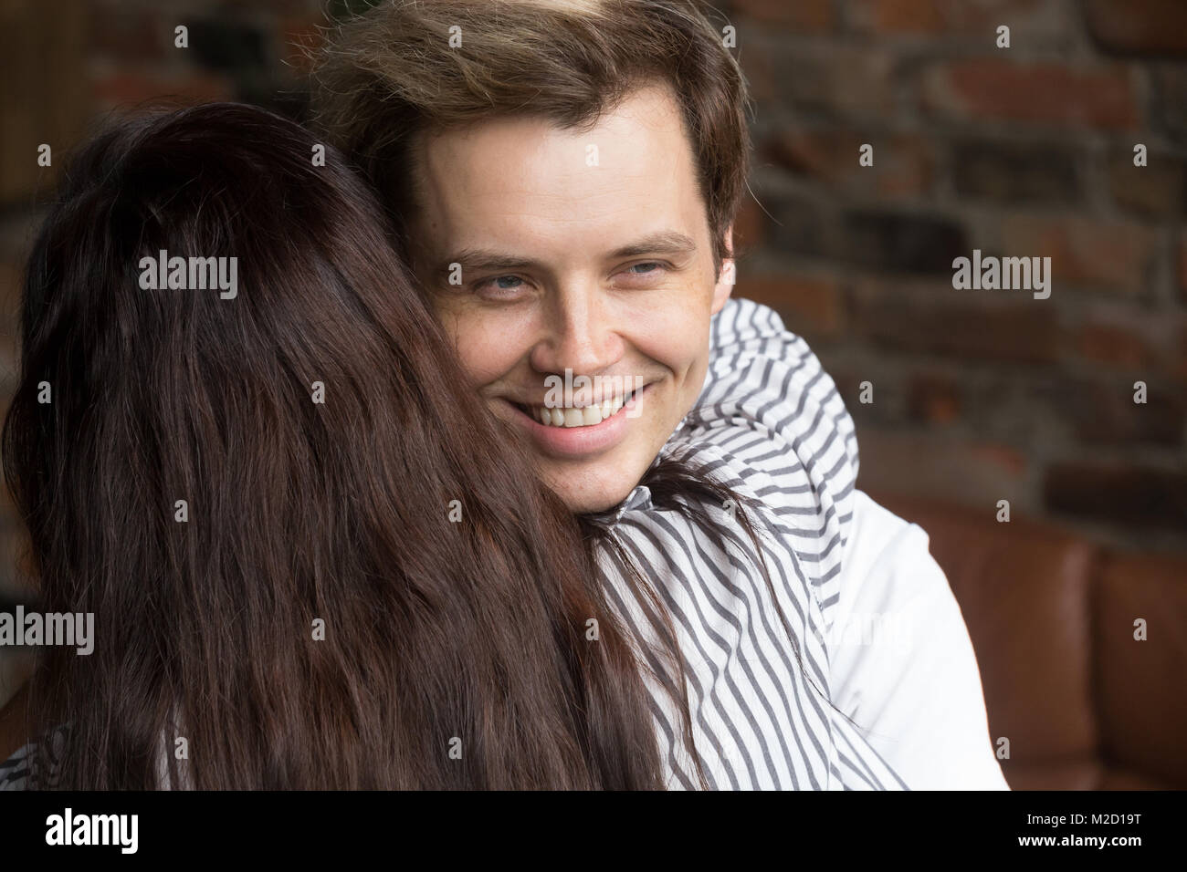 Young sly liar man happily smiling while woman embracing him - Stock Image