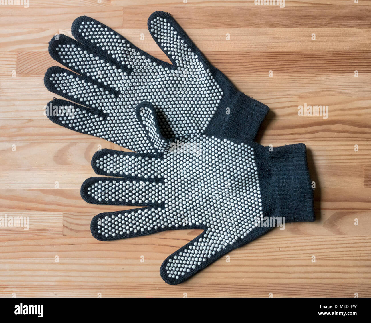 Navy blue woolen gloves with pebbled rubber palms for a better grip - Stock Image