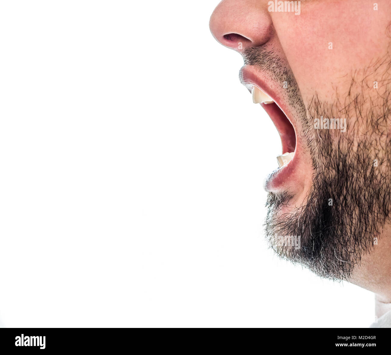 A mans face is seen in the image with his mouth wide open. He is positioned at the far right of the image with plenty - Stock Image