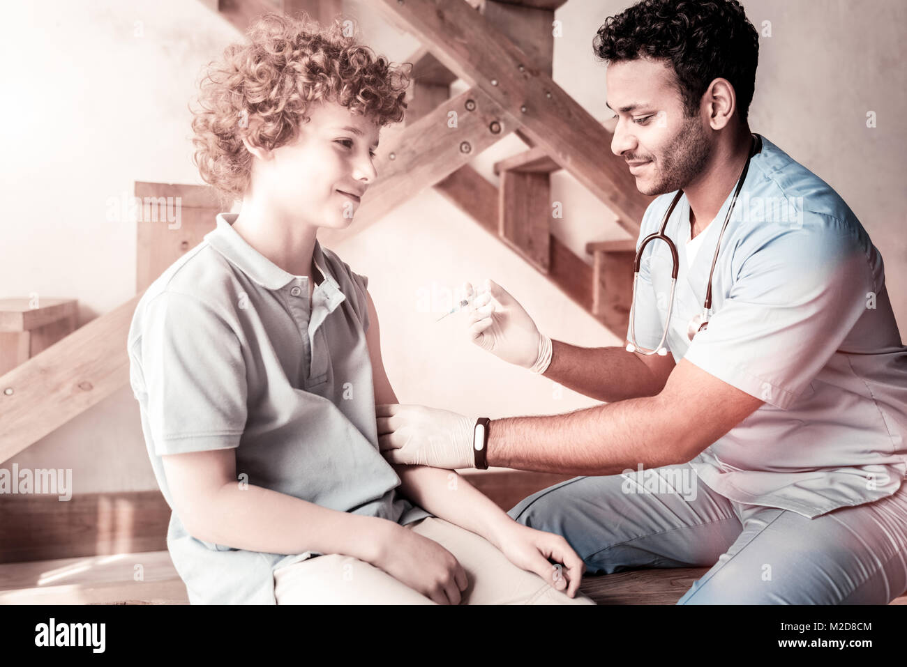 Male doctor vaccinating relaxed teen boy - Stock Image