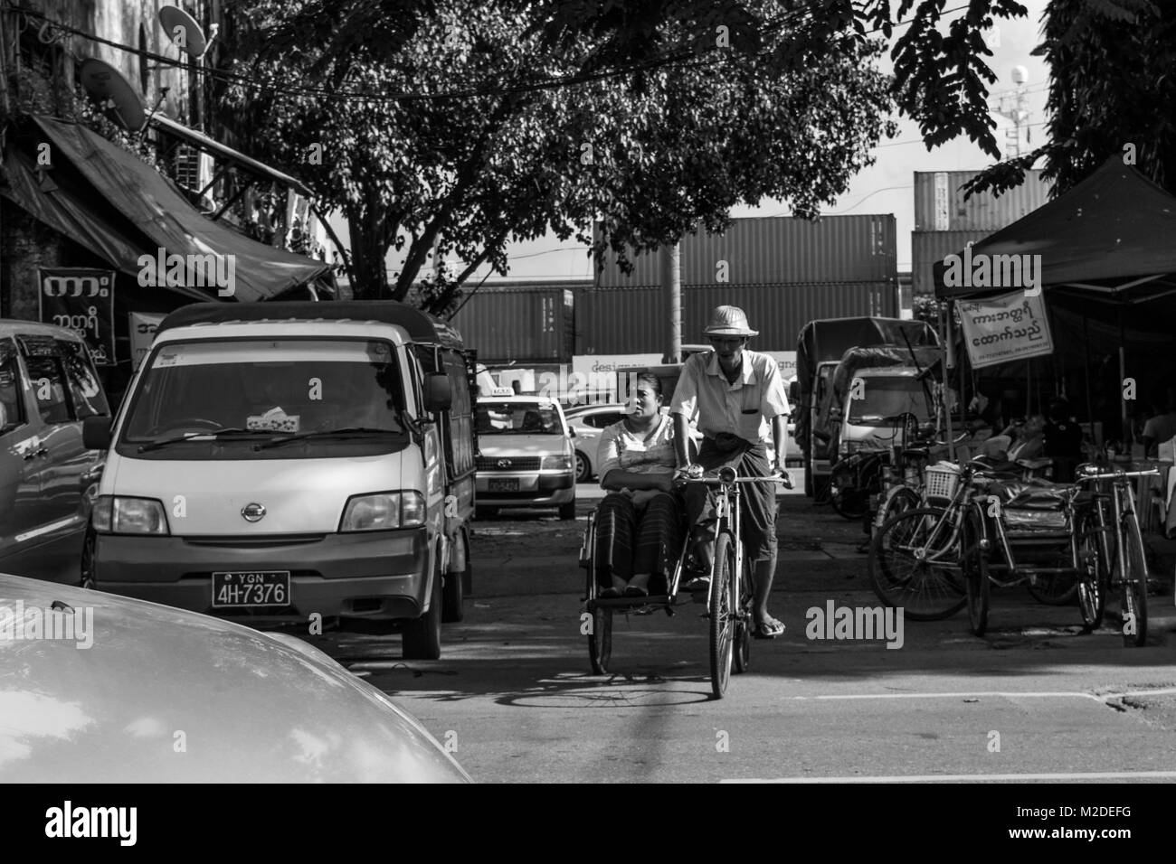 A Burmese couple, possibly husband and wife, with the man driving a cycle rickshaw in  the busy Yangon traffic and - Stock Image