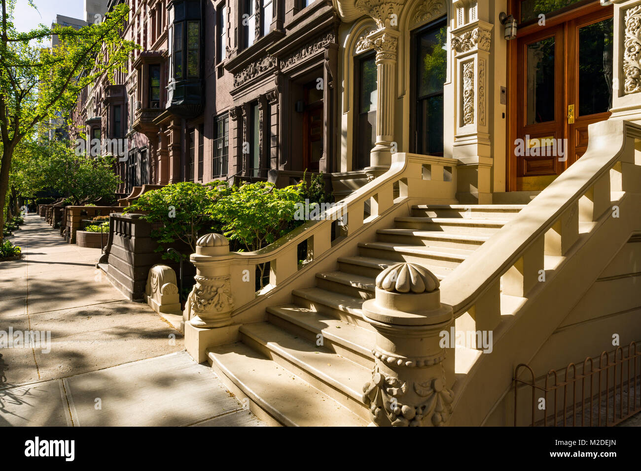Brownstones with doorsteps and ornament in morning light. Upper West Side Street, Manhattan, New York City - Stock Image