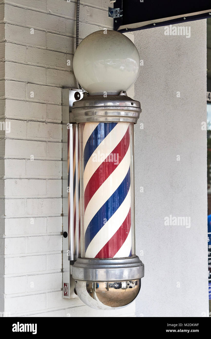 American barber pole on the exterior wall of a small town barber shop in Auburn Alabama, USA. - Stock Image