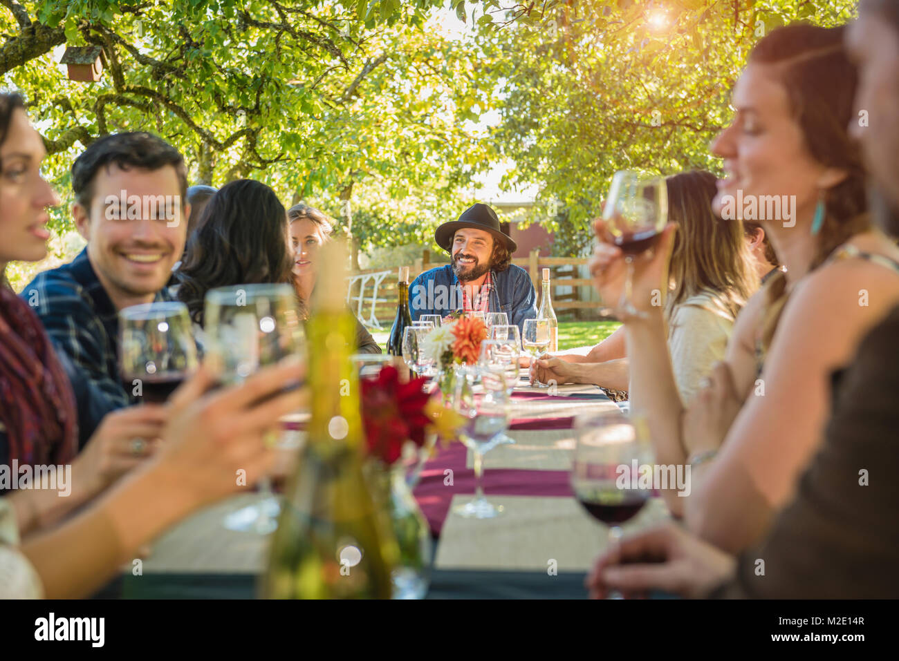 Friends drinking wine at party outdoors - Stock Image