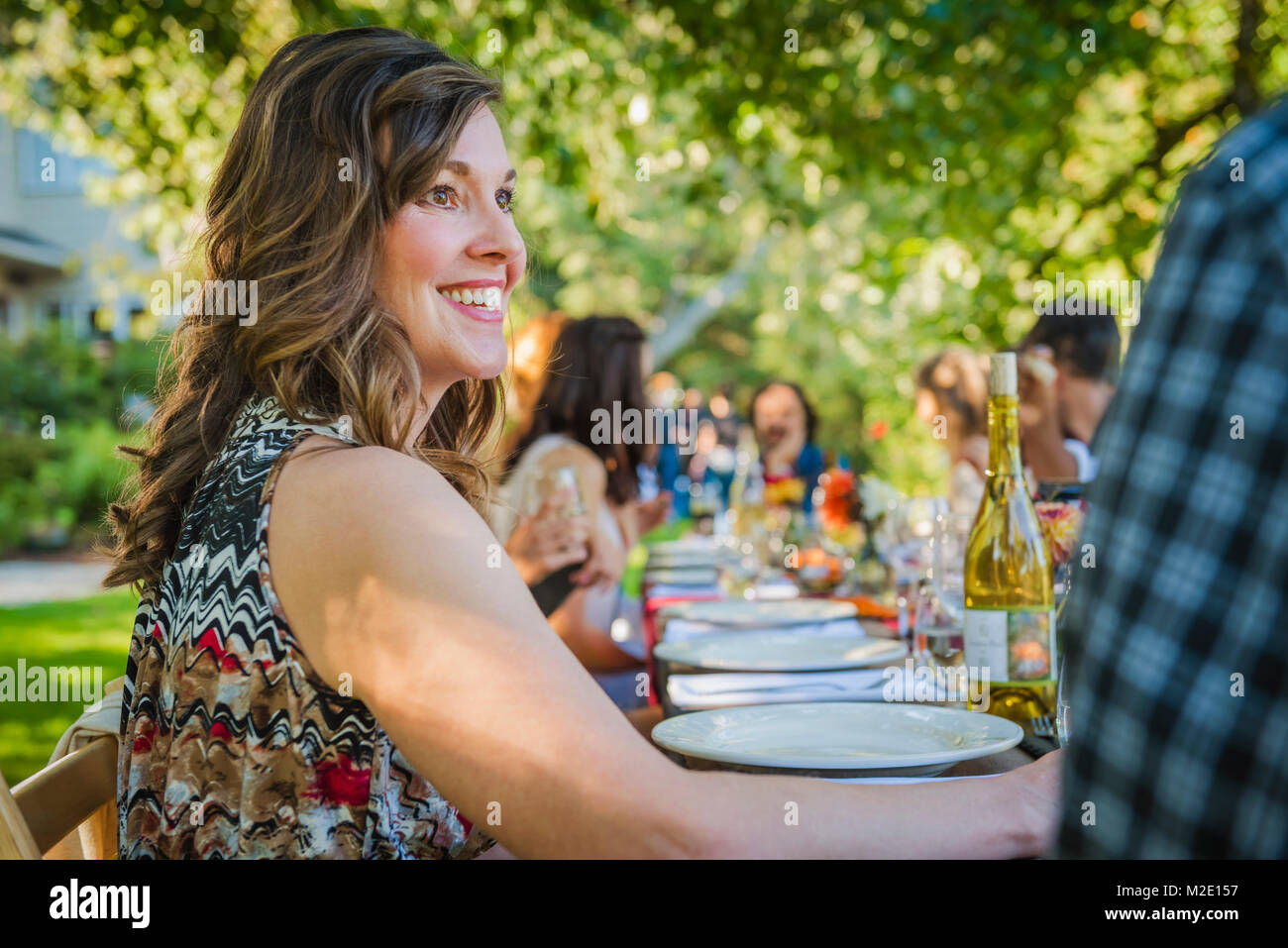Portrait of smiling Caucasian woman sitting at table at party outdoors - Stock Image