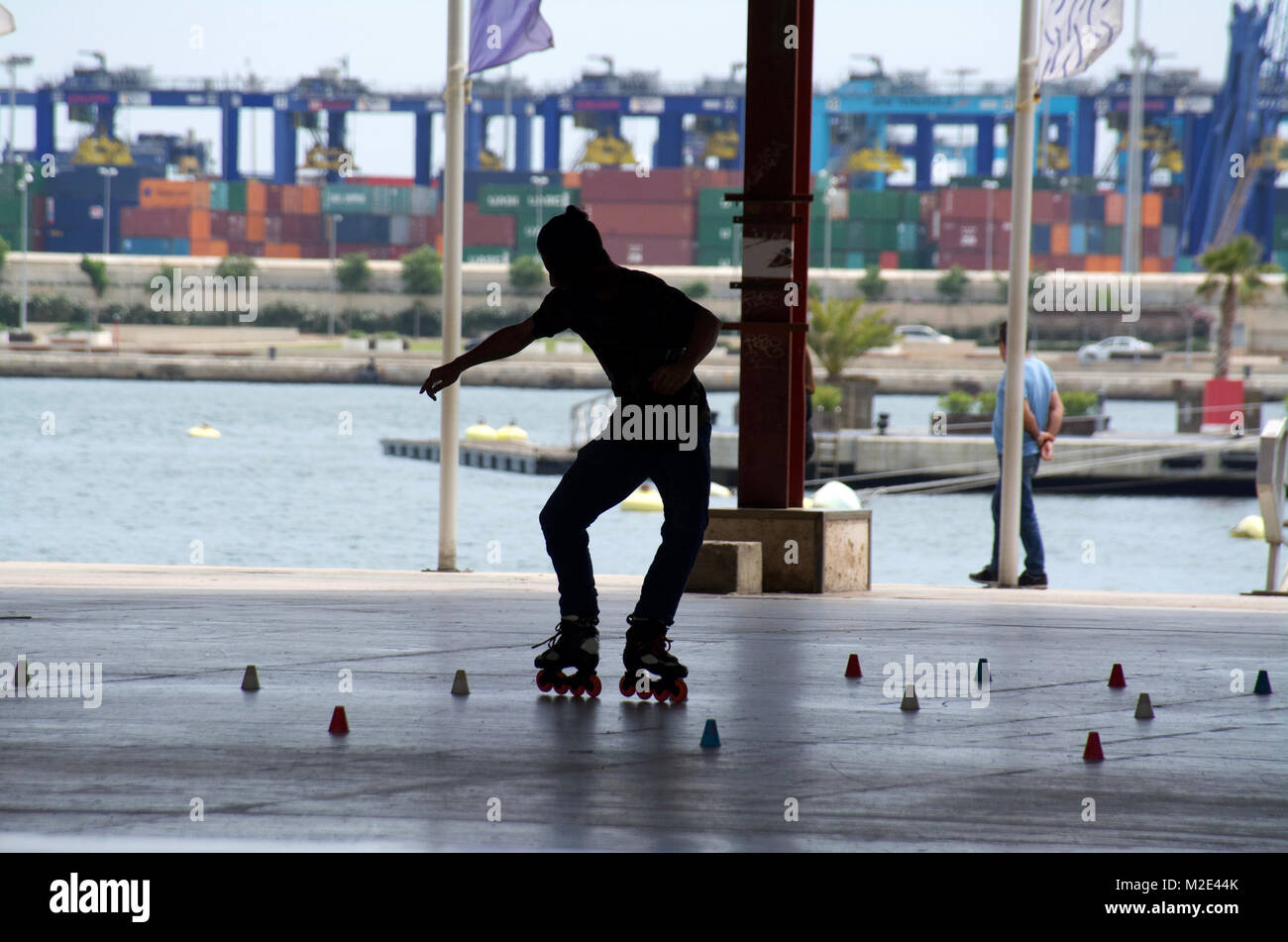 Skater Silhouettes at skate park in Valencia, Spain. Young & energetic rollerbladers enjoy the vigorous & - Stock Image
