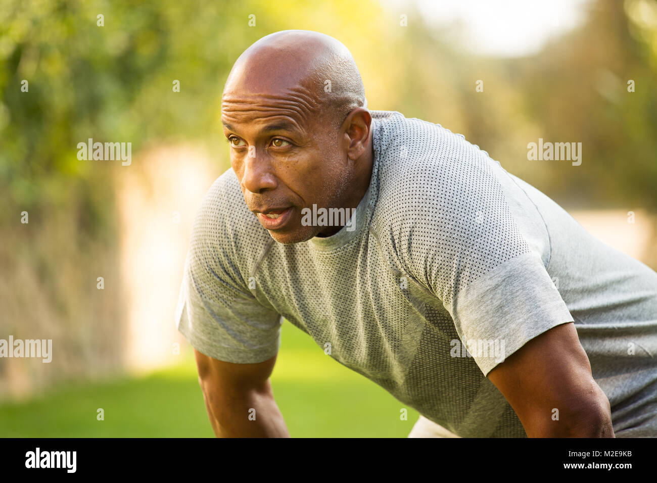Fit African American man lifting weights - Stock Image