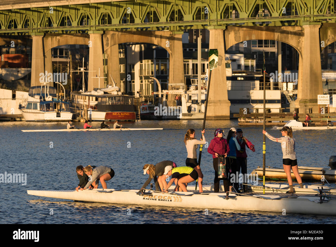 United States, Washington, Seattle, Women just back from a workout in rowing shells with the University Bridge in - Stock Image