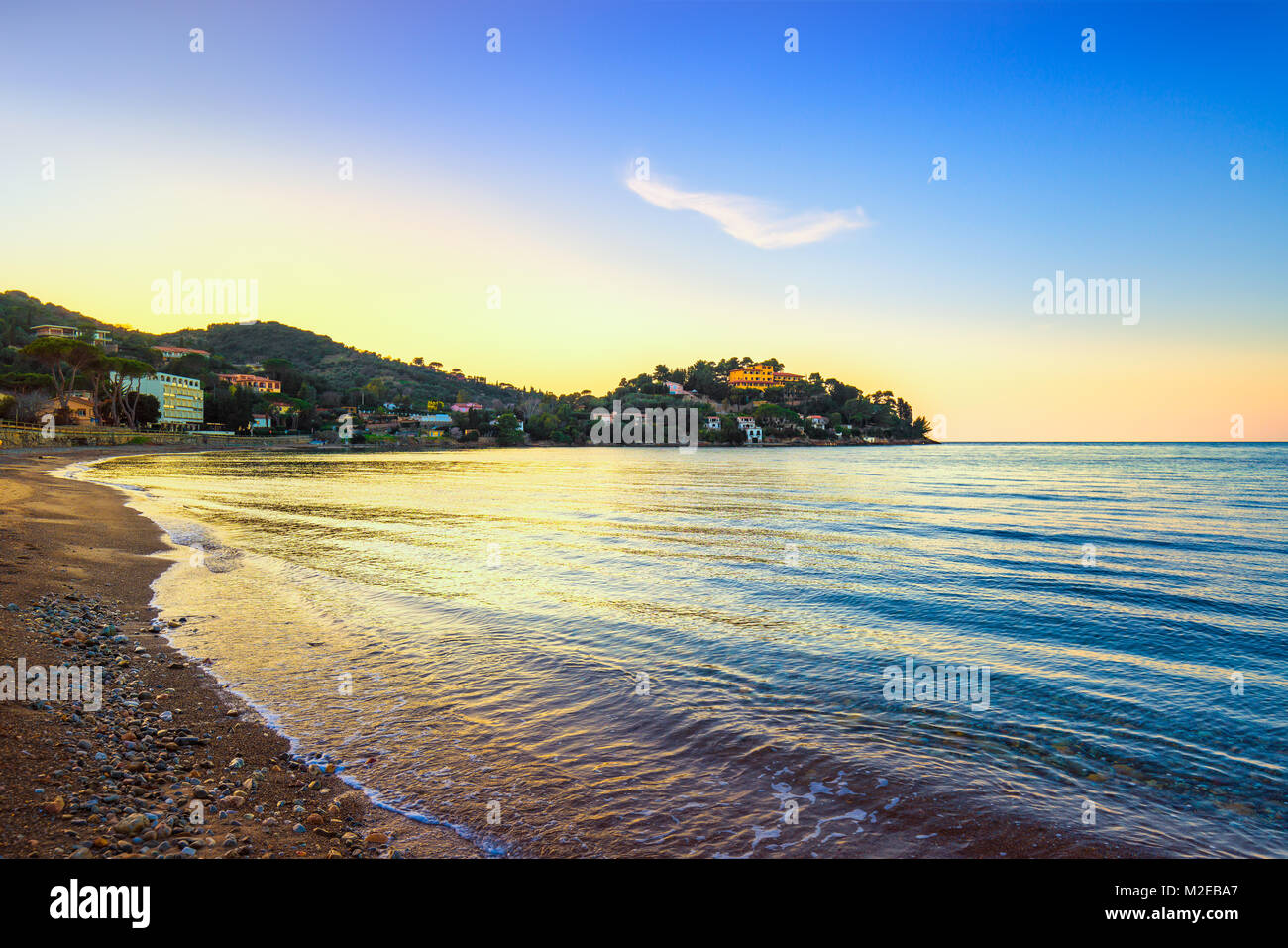Porto Santo Stefano, headland and bay beach at sunset in Monte Argentario, Maremma Tuscany, Italy - Stock Image