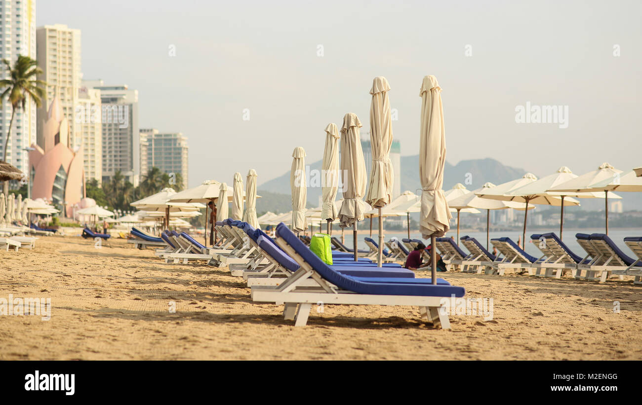 The employee spreads out the sun umbrellas. Nha Trang beach with many vacationing tourists. Vietnam. Timelapse. - Stock Image