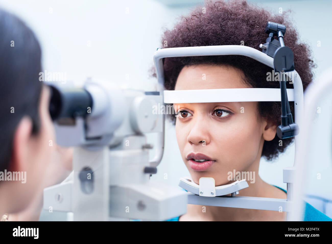 Optician measuring women eyes with refractometer - Stock Image